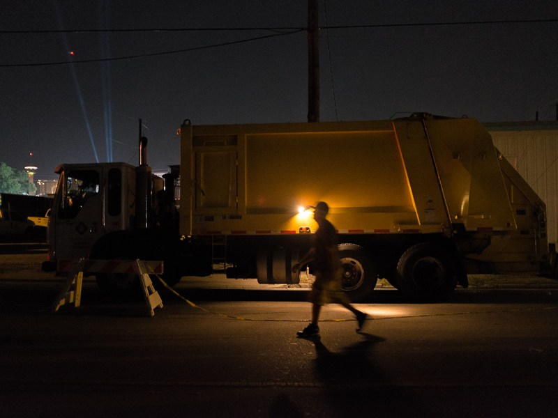 A man walks past a garbage truck that will be utilized in the cleanup during the Fiesta Flambeau Parade in downtown San Antonio. Photo by Scott Ball.