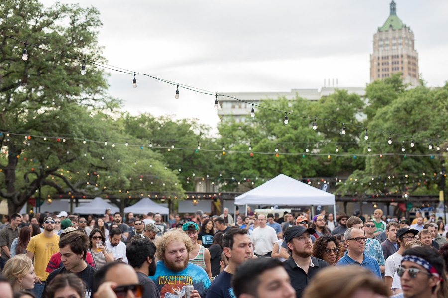 Festival attendees watch a performance at the La Villita Historic Arts Village as the Tower Life Building looms overhead during Maverick Music Festival 2015.