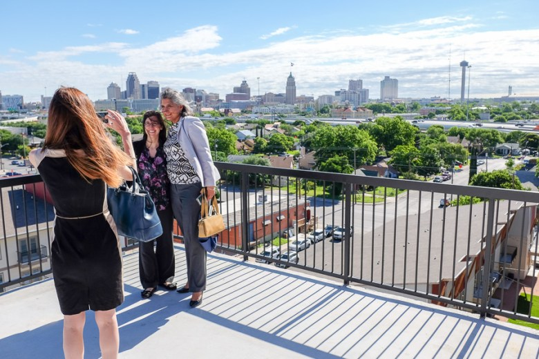 Members of the tour stop to take a photograph on a penthouse balcony at The Peanut Factory Lofts Ribbon Cutting. Photo by Scott Ball.