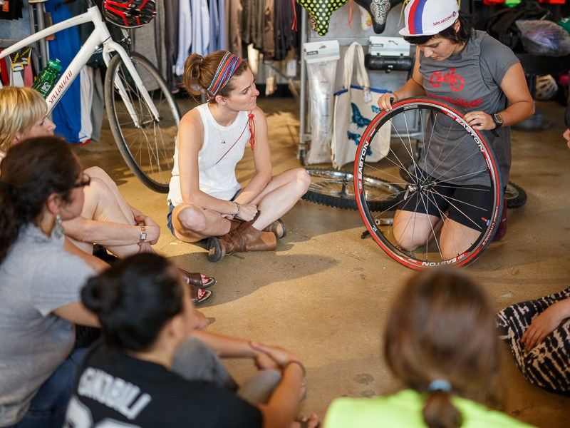 Edith Lopez Estrada demonstrates how to repair a flat during the third Women's Wrench Night at Bike World. Photo by Scott Ball.