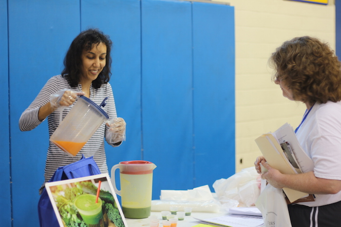 A volunteer hands out fresh-squeezed juice during the Heights Health Expo. Photo by Joan Vinson.