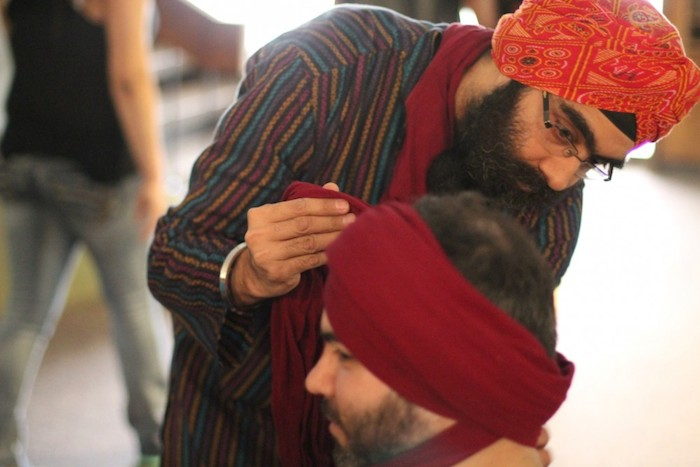 A man carefully ties a turban on a guest during the 2015 Asian Festival. Courtesy of Sikh Dharamsal.