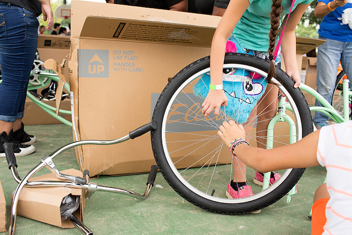 Two girls work as a team to place a bike frame on the front wheel during the Chiquitas Ciclistas event in the Eastside. Photo by Rachel Chaney