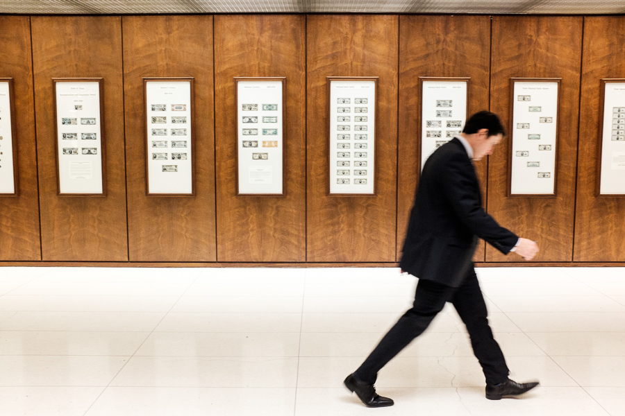 A man walks by a wall of currency at Frost Bank. Photo by Scott Ball.