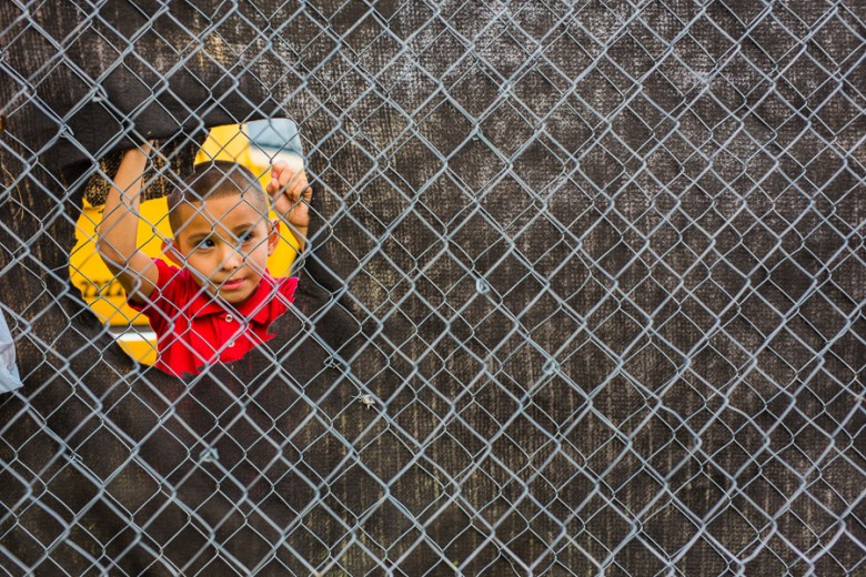 A boy looks through a hole in a fence to see the wrestling match. Photo by Scott Ball.