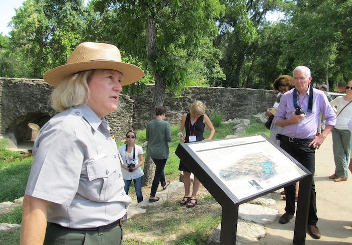 Archaeologist Susan Snow of San Antonio Missions National Historical Park speaks to ICOMOS symposium visitors at Espada Aqueduct in May 2012. Photo by Carol Baass Sowa / Today's Catholic.