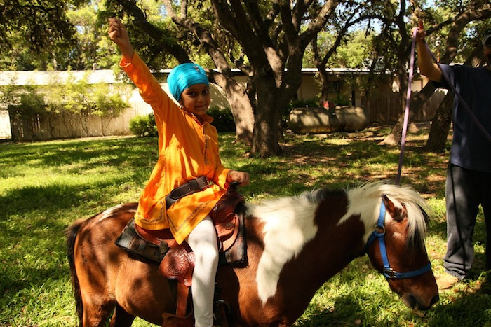Children ride ponies during Vaisakhi at Sikh Dharamsal. The festival celebrates the founding of the Sikh community every April 14. Photo courtesy of Sikh Dharamsal.