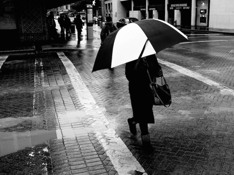 A woman carries an umbrella across Saint Mary's Street. Photo by Scott Ball.