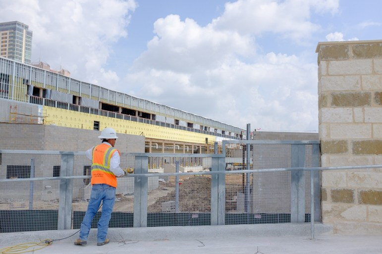A construction worker looks over the pedestrian bridge. Photo by Scott Ball.