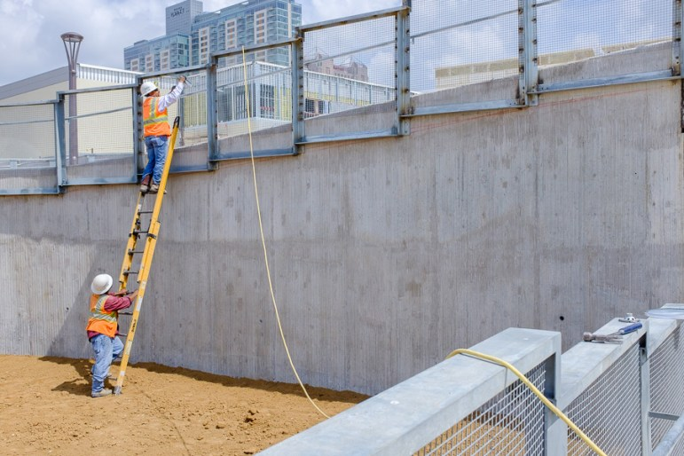 Construction workers paint a railing on the new pedestrian bridge. Photo by Scott Ball.