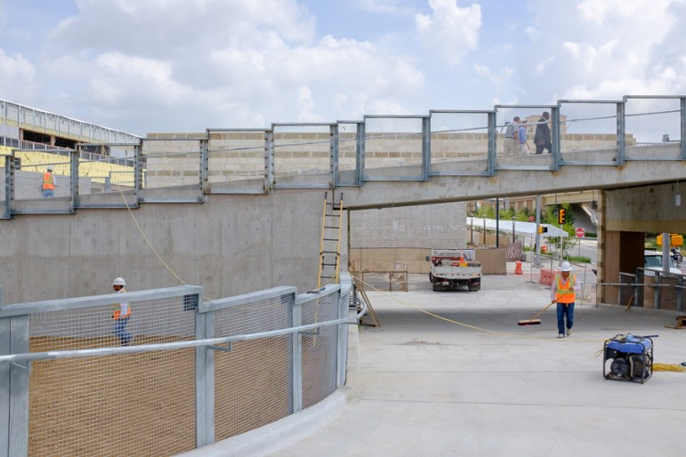 Construction workers and pedestrians on the pedestrian bridge. Photo by Scott Ball.