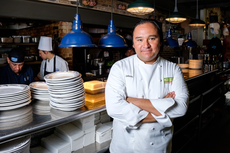 Chef Johnny Hernandez poses for a photo in front of the line at La Gloria. Photo by Scott Ball.