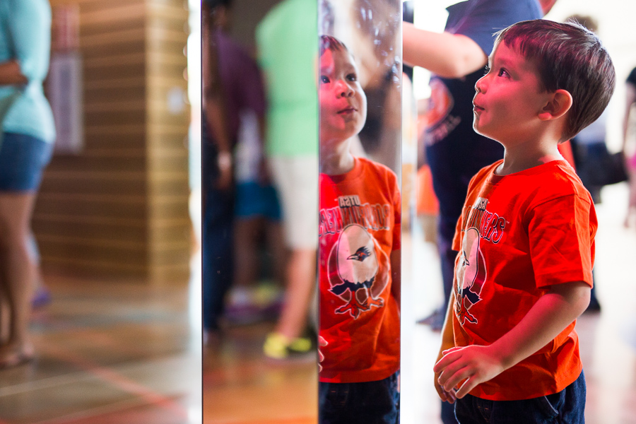 A boy plays with spinning mirrors. Photo by Scott Ball.