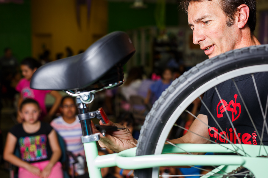 Cristian Sandoval teaches how to adjust a bicycle seat post. Photo by Scott Ball.