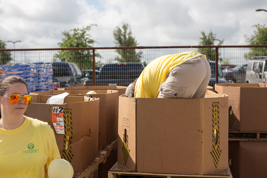 A volunteer grabs the remaining cantaloupes before moving on to a new box. Photo by Scott Ball.