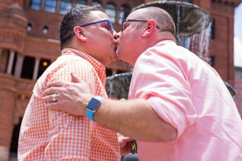 Frankie Ortiz (left) and Brandon Hughes kiss in front of the Bexar County Courthouse. Photo by Scott Ball.