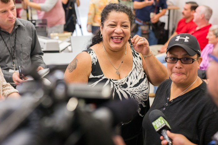 Lisa Santiago and Veronica Uviedo answer questions from reporters while waiting in line to apply for a marriage license. Photo by Scott Ball.