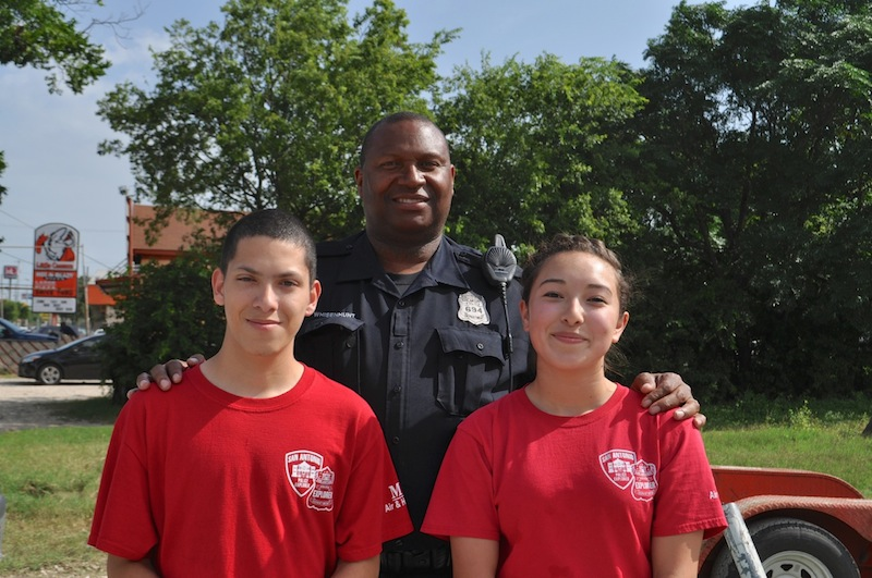 Robert Rodriguez, 18-year-old Edison High School student, Officer Kevin Whisenhunt, and Zulema Rodriguez, 15-year-old Brackenridge High School, pose for a photo. Zulema and Robert (no relation) both want to police officers and are taking part in the SAPD Explorer program. Photo by Iris Dimmick.