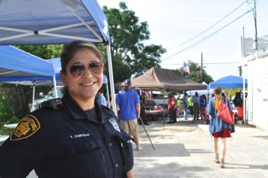 Officer Tina Castillo stands in the shade as a line forms for food. Photo by Iris Dimmick.