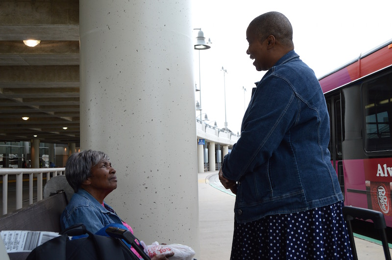 L to R: Fernande Mercier and her companion, who flew in from Los Angeles for the 7th Day Adventist convention, wait for the VIA bus to arrive and take them downtown on Thursday, July 2, 2015. Photo by Lea Thompson.