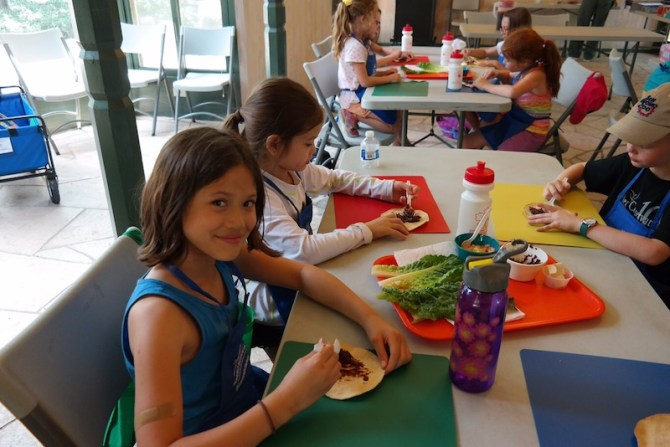 A child poses for a photo while making a refried black bean tostado with quest fresco, lettuce, tomato, and avocado. Courtesy photo.