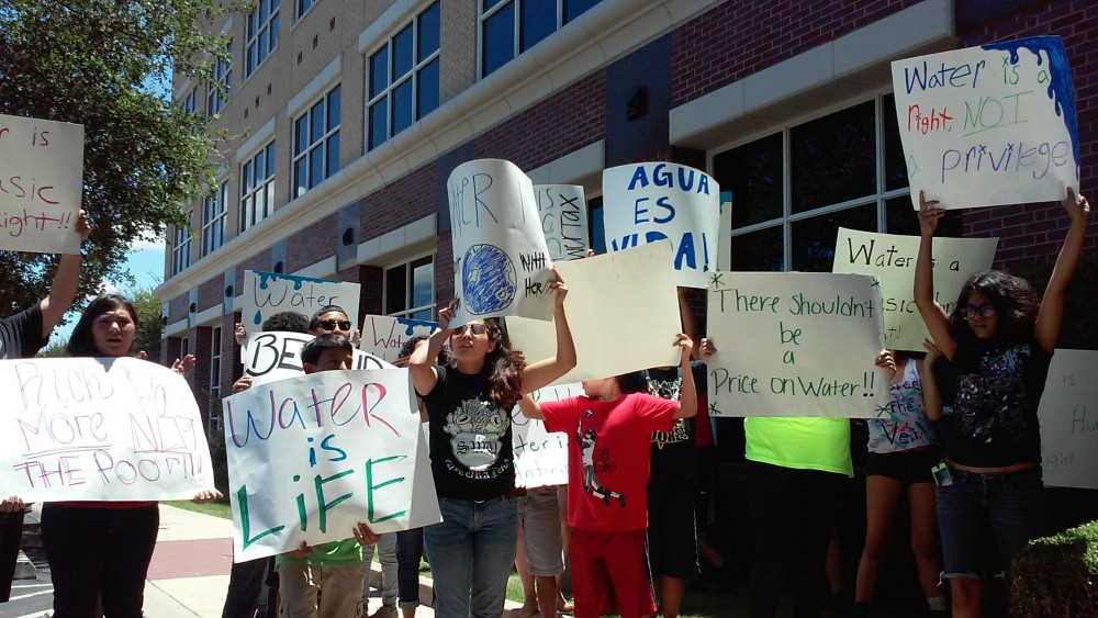People from local organizations, guided by the Texas Organizing Project, protest a meeting about the San Antonio Water System's proposed new rate structure at the SAWS campus on Wednesday, July 15, 2015. Photo by Edmond Ortiz