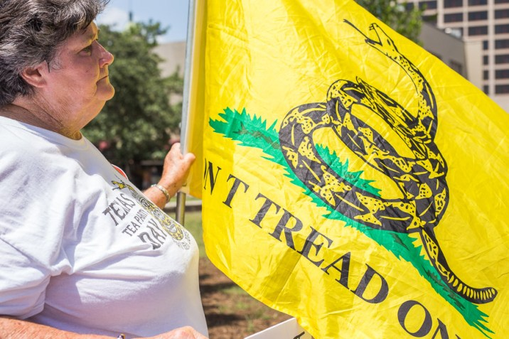 Maggie Wright holds the Gadsden flag while listening. Photo by Scott Ball.