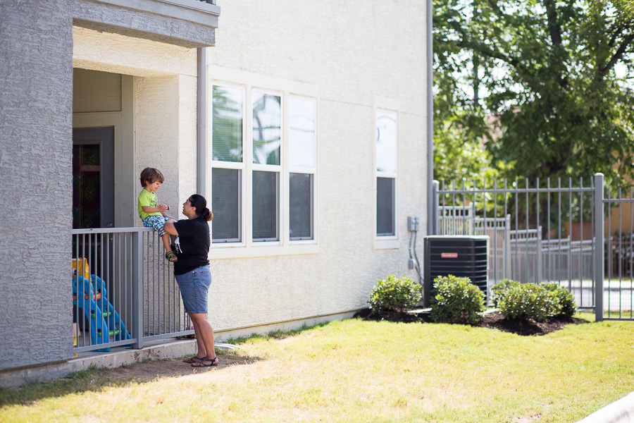 A woman and her child spend time together outside of their apartment at San Juan Square. Photo by Scott Ball.