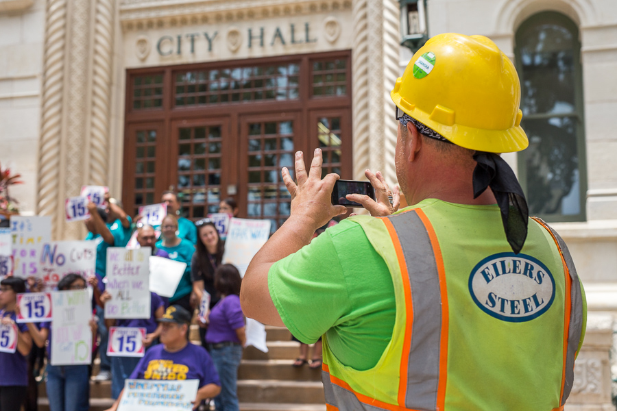 A worker takes a photo of the public protest in front of city hall. Photo by Scott Ball.