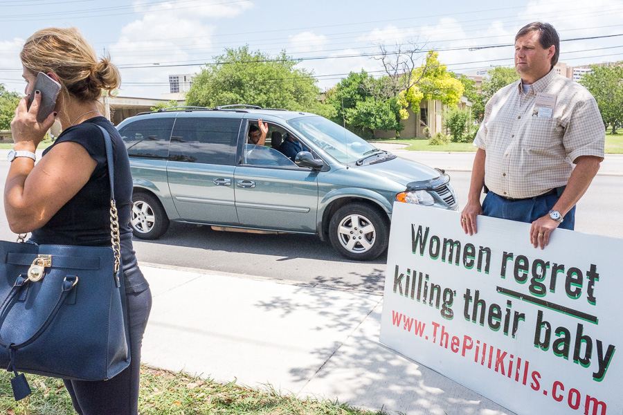 Patrick Von Dohlen (right) looks on as Linda Mansouri calls the police outside of Planned Parenthood. Photo by Scott Ball.