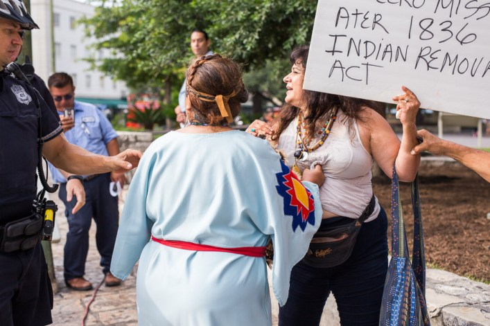 Gloria Pacheco Hernandez (left) holds protestor Mary Torres as a police officer intervenes during a physical altercation. Photo by Scott Ball.