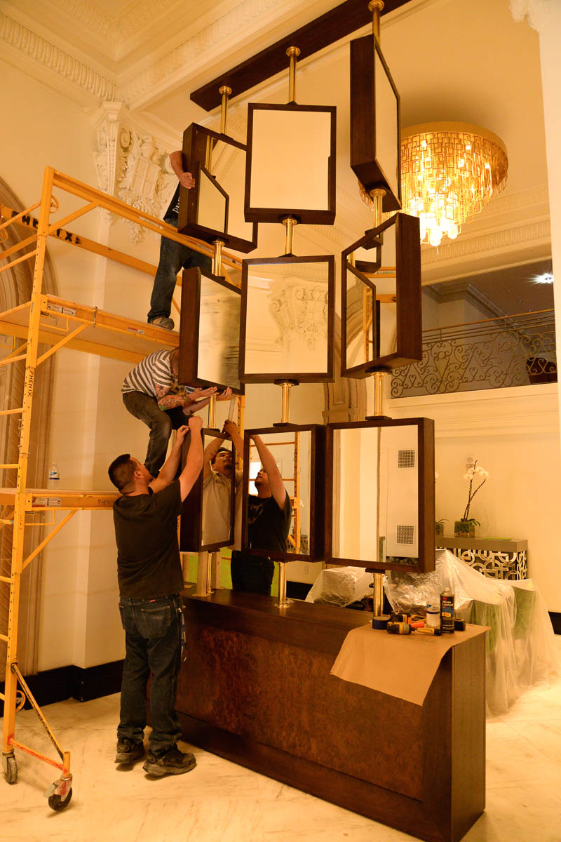 Workers put the finishing touches on a display in the main lobby near The St. Anthony Hotel registration desk. Photo by Annette Crawford.