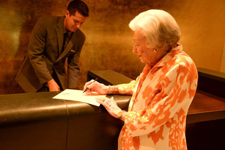 Amanda Ochse registers as the re-opened hotel's first official guest at 2:30 p.m. July 21, 2015, prior to the start of the reception at The St. Anthony Hotel. Ochse is the widow of former hotel owner William Ochse. Photo by Annette Crawford.