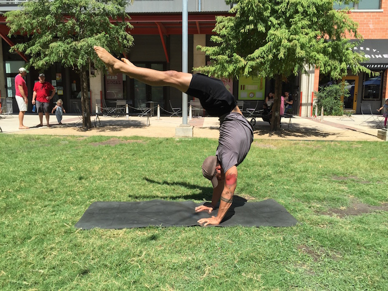 Yoga on the Green: Eric Muñoz demonstrates a Mexican Hollow Back handstand. Photo by Robert Rivard/