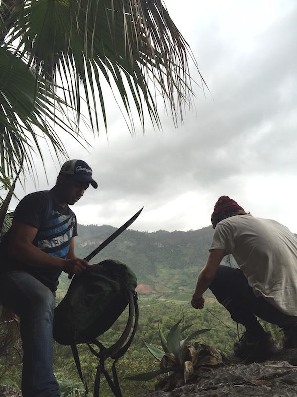 Otto, right, and Darwin, left, preparing to sit out a rainstorm after we spent the day exploring caves outside the village. Photo by Everett Redus.