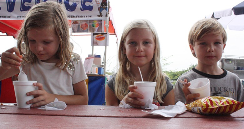 The Johnson children, Amelia (left), Eleanor, and Lian, enjoy a treat at Raspa Fest 2015. Photo by Kay Richter.