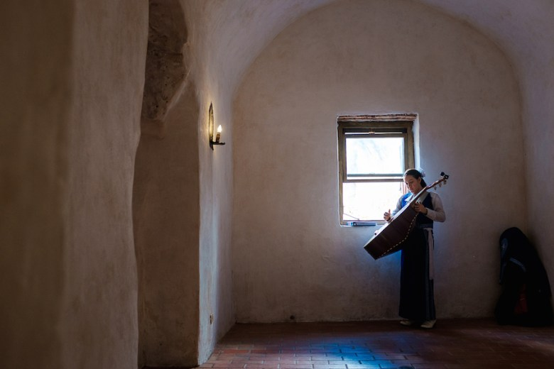 Desiree, age 14, practices on her guitaro before a mariachi performance at Mission Concepción. Photo by Scott Ball.