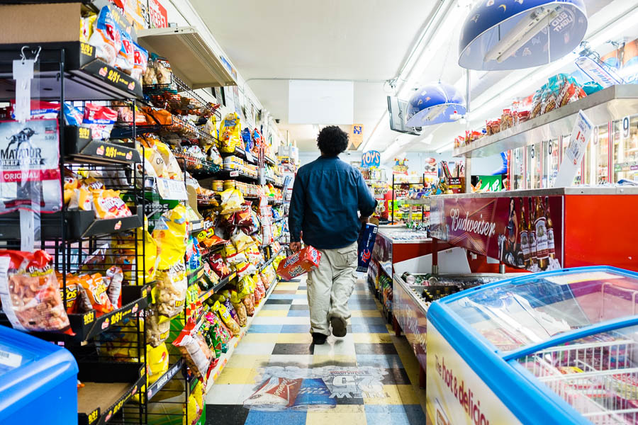 Matt Perry, an employee of Express Mart #4, walks through the aisle to restock cans of soda. Photo by Scott Ball.