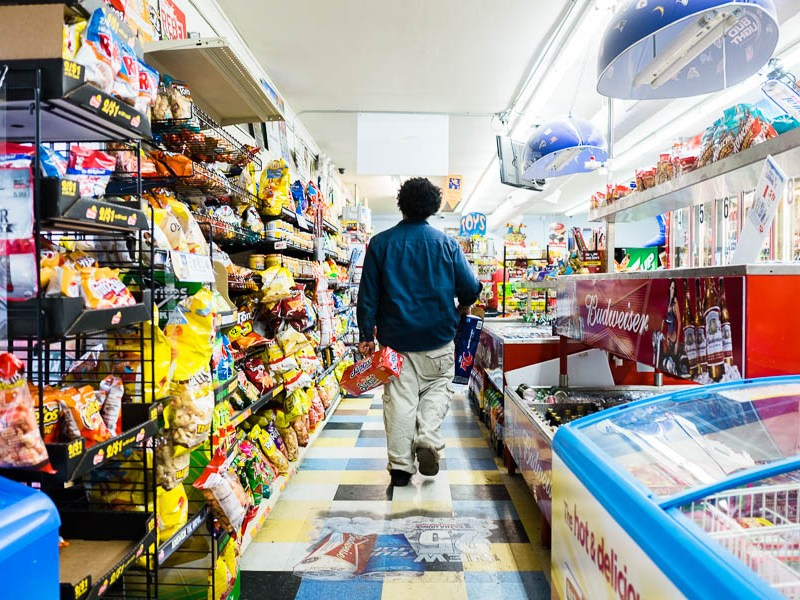 Matt Perry, an employee of Express Mart #4, walks through the aisle to restock cans of soda. Photo by Scott Ball.