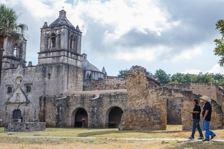 Ramón Vásquez and Jesús Reyes traverse the grounds at Mission Concepción. Photo by Scott Ball.
