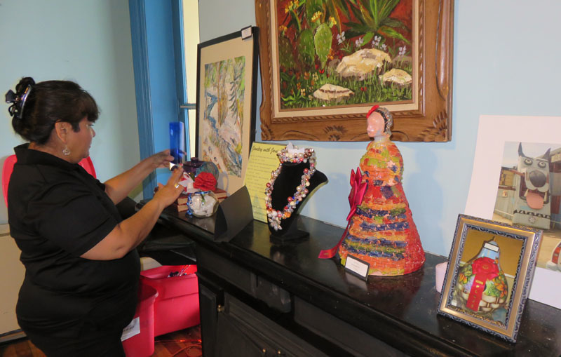 Gloria de la Cruz-Sandoval arranges art pieces for the ArtAbility shot. Photo by Warren Lieberman.
