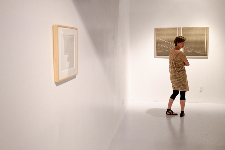 A guest looks at artwork hung on gallery walls. Photo by Scott Ball.