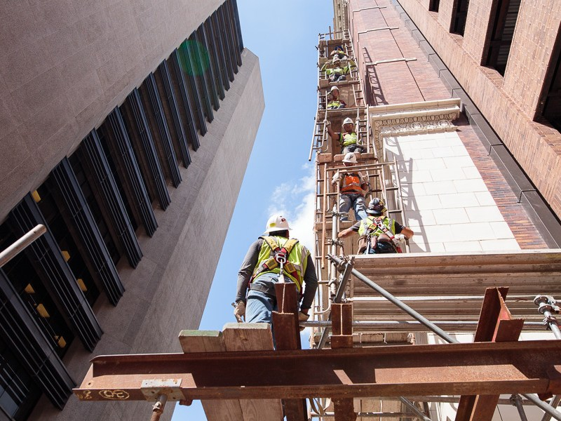 Workers take scaffolding down piece by piece on the west side of the historic Rand Building. Photo by Scott Ball.
