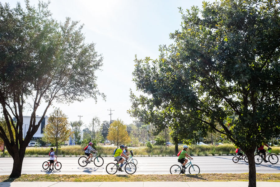 Cyclists ride past Lions Field. Photo by Scott Ball.