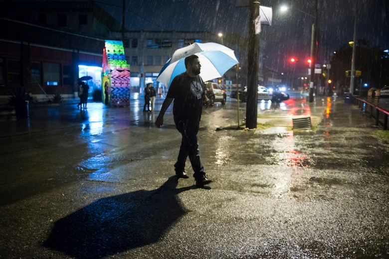 An attendee walks to the main stage under his umbrella during Luminaria. Photo by Matthew Busch.