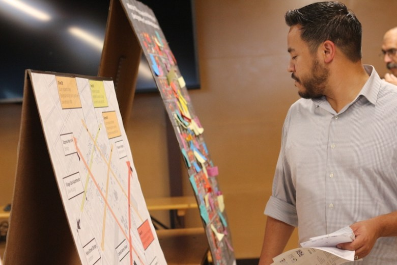 An attendee examines the exhibits and place making maps for the Place Changing project. Photo by Joan Vinson.