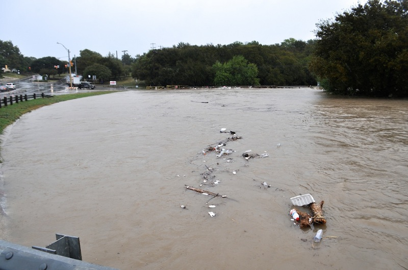 Trash is carried by flood waters down a drainage ditch near the Alamo Quarry Market. Photo by Iris Dimmick.
