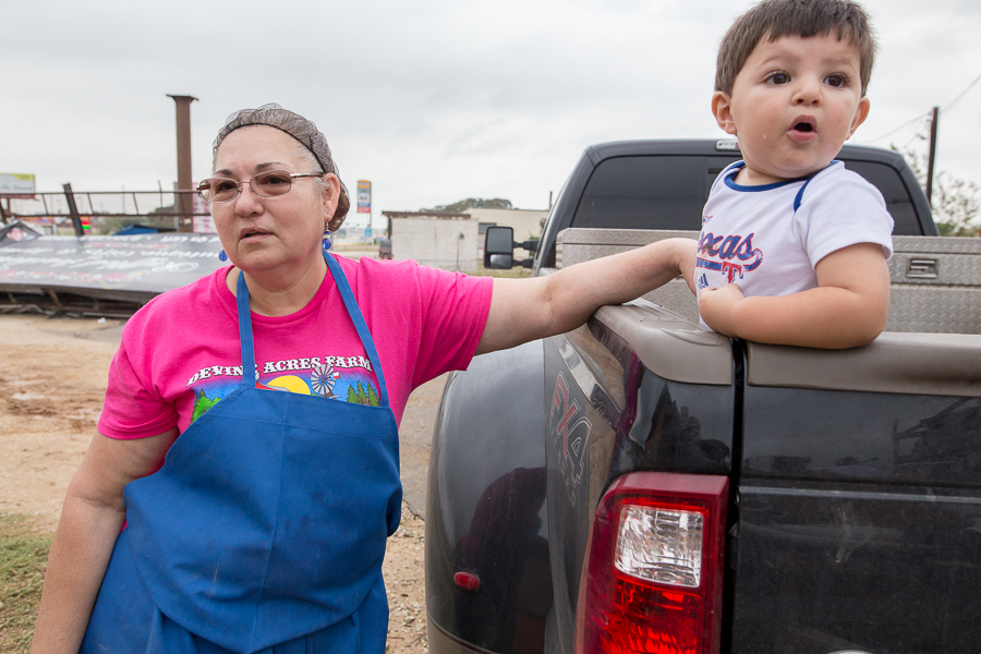 Owner of Veliz Taqueria Arazely Veliz comforts her grandson Juan Carlos as a portion of the building is taken down. Photo by Scott Ball.