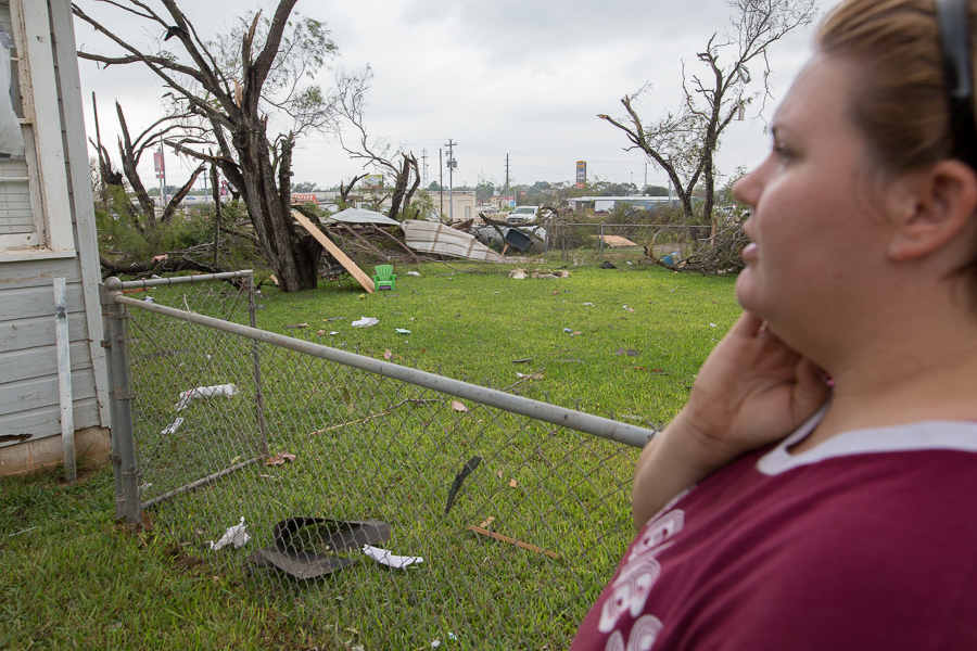 Courtney Chilek looks at the destruction caused to her home. Photo by Scott Ball.