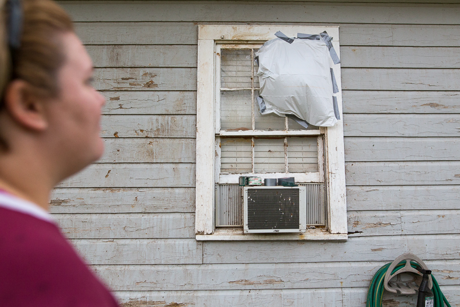Courtney Chilek looks at a bedroom window that was broken by the tornado. Photo by Scott Ball.
